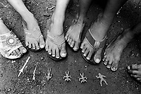 Philippines. National Capital Region. Manila. Paradise village. Childreen feet, flip-flops sandals and plactic war toys. Paradise village has a population of 15'000 people and is a part of Barangay Tonsuya situated on Lettre Road in Malabon. Manila is part of the National Capital Region (NCR) on Luzon island. Manila is the capital of the Philippines and one of the sixteen cities that comprise Metro Manila. Metro Manila is the most populous metropolitan area in the Philippines. Flip-flops, zoris, Hawaii chappal, thongs, Japanese sandals, or jandals are an open type of outdoor footwear, consisting of a flat sole held loosely on the foot by a Y-shaped strap, like a thin thong, that passes between the first (big) and second toes and around either side of the foot. Flip-flops may also be held to the foot with a single strap over the front of the foot rather than a thong. They are called 'Flip-flops' because of the noise they make, slapping against the heel, while walking. © 1999 Didier Ruef