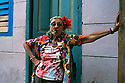 A woman who identified herself simply as Graciela puffs on a cigar in Havana, Cuba as she strikes a jaunty pose on a Sunday morning in 2001. Prints of this image are for sale.  freelance photo by Bill Wechter