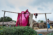 25 year old Sri Kanthi Devi carries on with her daily chores, here she dries the clothes outside her house in Ramgarwa village in Raxaul district in Bihar, India.