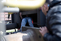Pictured: A migrant man attempts to hide himself in the under carriage of a train at the OSE freight depot in Thessaloniki, Greece. Wednesday 05 April 2017<br /> Re: A year after an agreement was signed between Greece and Turkey for the management of refugees. Migrants, mostly from Morocco, Algeria and Tunisia, have been living in disused train carriages at the Thessaloniki freight depot of OSE in northern Greece, the company managing the railways in the country. Some of the migrants climb onto moving trains, or even hide themselves in storage areas, hoping that they will cross the border.