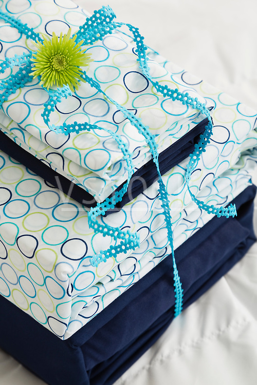 Stack of bedding set with blue ribbon and flower head