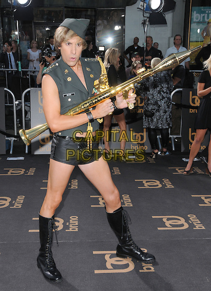"SACHA BARON COHEN.The Universal Pictures' L.A. Premiere of ""Bruno"" held at the Grauman's Chinese Theatre in Hollywood, California, USA. .June 25th, 2009.full length army green uniform military gold chanel bazooka rocket launcher gun boots hat posing mouth open .CAP/DVS.©Debbie VanStory/Capital Pictures."