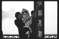 A tourist holds a toddler girl at the West Lake in Hangzhou, Zhejiang province, China, March 2013.