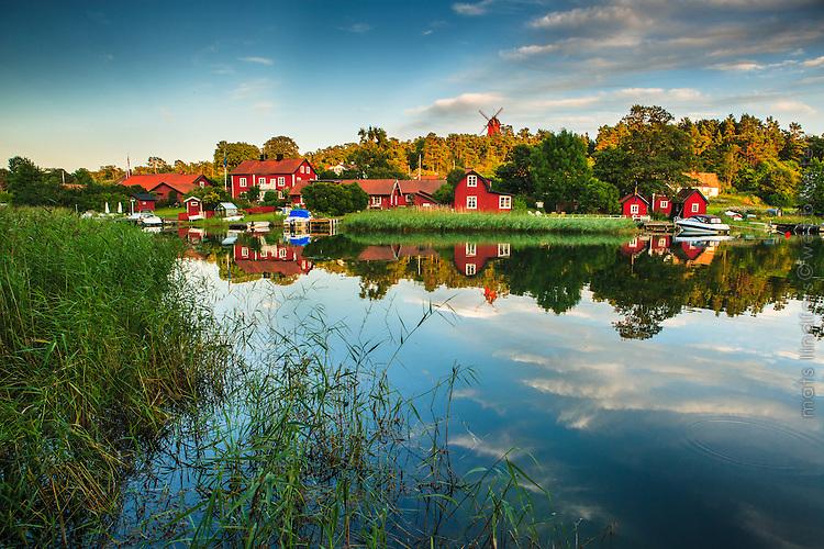 Stugor hus och väderkvarn speglas i vattnet på Utö i Stockjholms skärgård