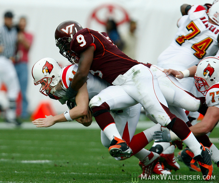 Virginia Tech linebacker Vince Hall (9) and defensive tackle Jonathan Lewis (hidden) combine for a sack of University of Louisville quarterback Hunter Cantwell that resulted in Cantwell leaving the game for one play before returning with a broken nose in the Toyota Gator Bowl January 2, 2006 in Jacksonville, Florida.     (Mark Wallheiser/TallahasseeStock.com)