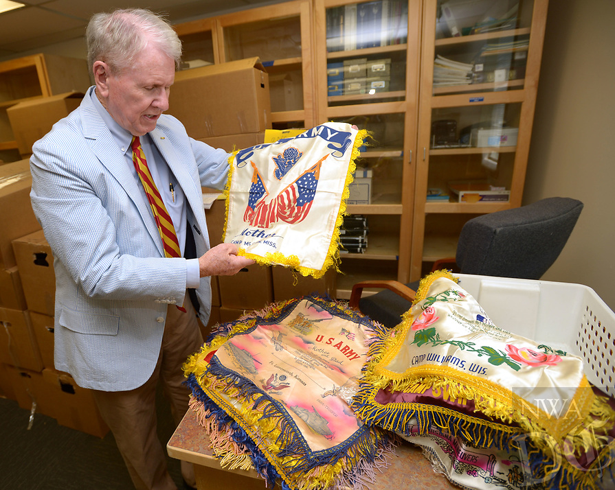 NWA Democrat-Gazette/ANDY SHUPE<br /> Jim Johnson, vice president for development at the Arkansas Air and Military Museum at Drake Field in Fayetteville, shows off one of 50 World War II- and Korean War-era pillow slips that were donated to the museum. The slips were common mementos that were purchased by U.S. service members to send home to family or significant others from military bases and theaters of operation. The collection will soon be displayed at the museum.