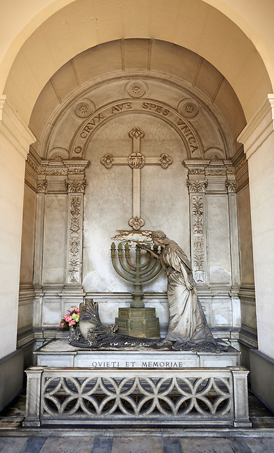 Picture and image of the stone sculpture of a young women filling a candle stick with oil in an art Nouveau style. Family Tomb Montanari sculpted by G B Villa 1888. Section D no 31 the monumental tombs of the Staglieno Monumental Cemetery, Genoa, Italy