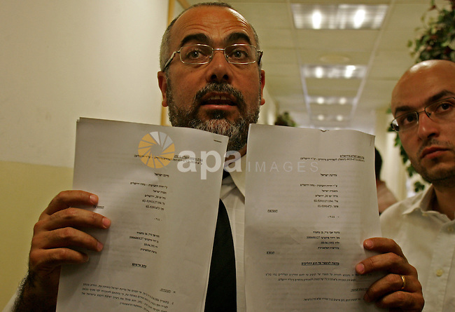 Palestinian Hamas lawmaker displays papers to media after Muhammad Abu-Teir arrives at the courtroom at the magistrate's court in Jerusalem July 1, 2010. Israeli police arrested Abu-Teir in his Jerusalem neighbourhood on 30 June, saying he was there illegally after Israel revoked his residency permit over his hardline Islamist affiliation. The arrest of Abu-Teir looked likely to sharpen international criticism of the Jewish state's plan to deport him along with three other Hamas politicians from East Jerusalem. Photo by Mahfouz Abu Turk
