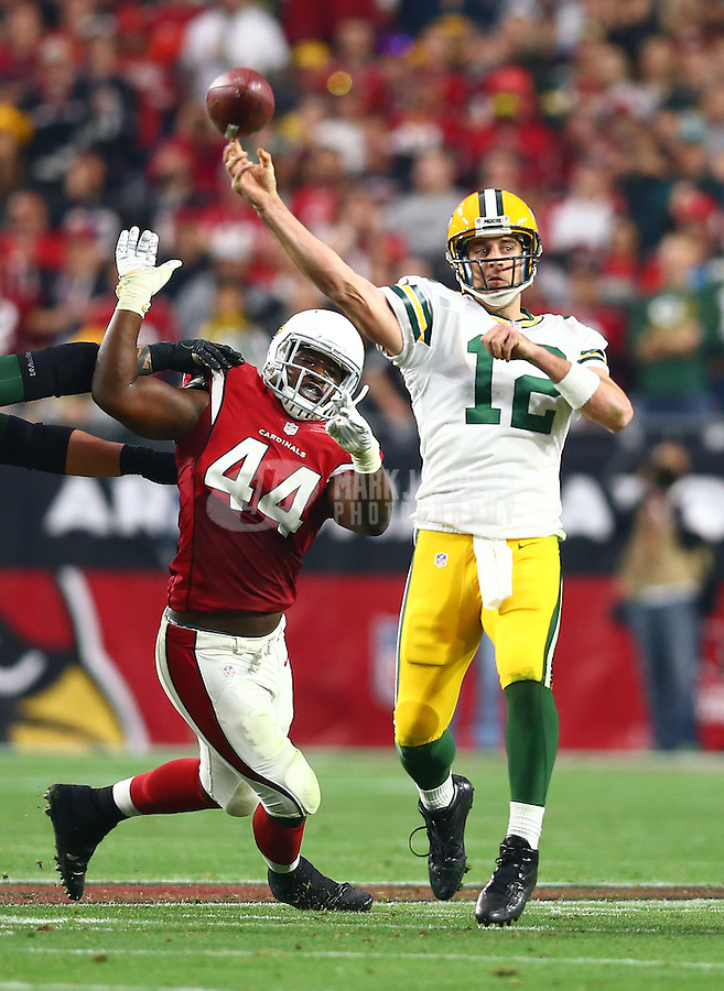 Dec 27, 2015; Glendale, AZ, USA; Green Bay Packers quarterback Aaron Rodgers (12) throws a pass under pressure from Arizona Cardinals linebacker Markus Golden (44) at University of Phoenix Stadium. The Cardinals defeated the Packers 38-8. Mandatory Credit: Mark J. Rebilas-USA TODAY Sports