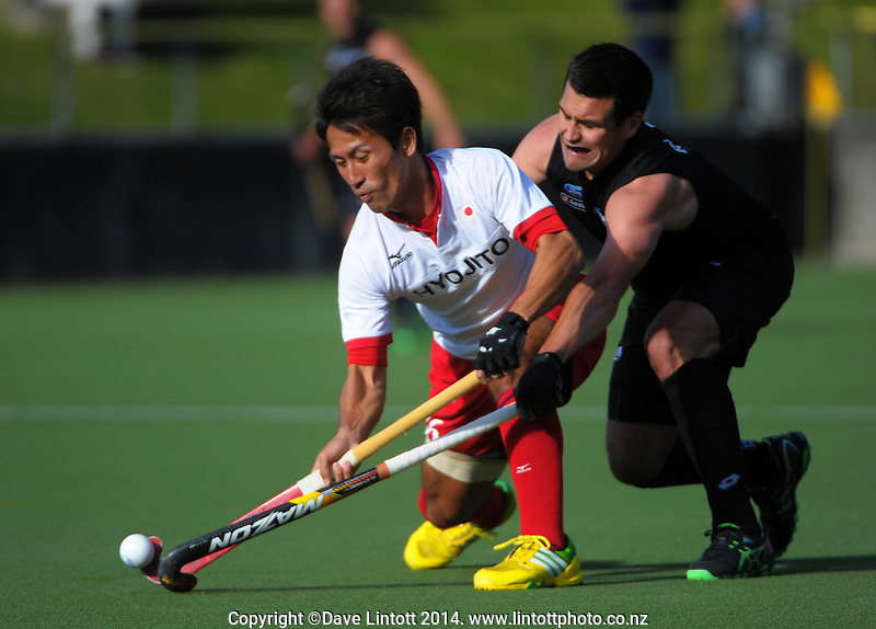 Nick Ross tries to tackle Kazuma Murata during the international men's hockey match between the NZ Black Sticks and Japan at National Hockey Stadium, Wellington, New Zealand on Tuesday, 18 November 2014. Photo: Dave Lintott / lintottphoto.co.nz