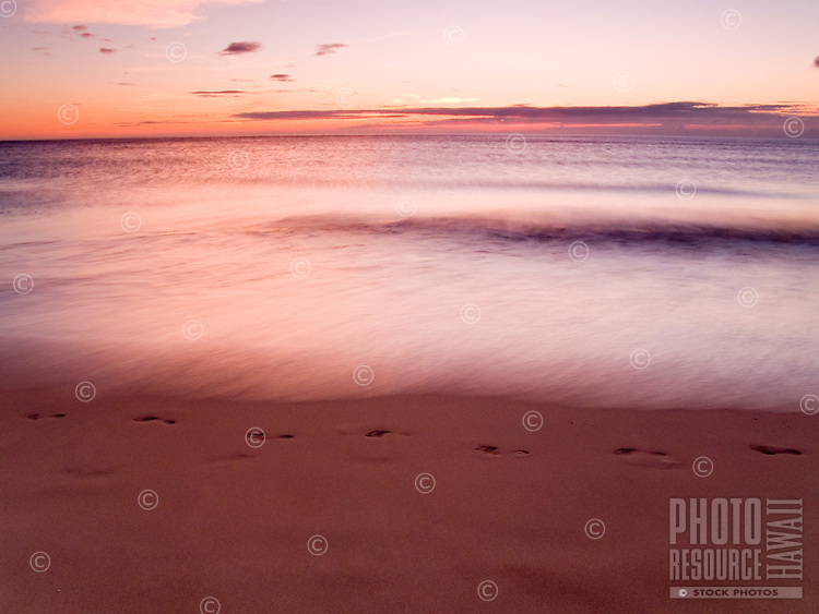 Footprints in the sand at Hapuna Beach during a sunset, Big Island.