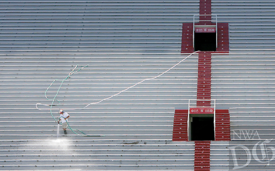 NWA Media/DAVID GOTTSCHALK - 6/24/14 - Renaldo Sanchez, with the University of Arkansas at Fayetteville Maintenance Department continues to spray wash the bleachers Tuesday June 24, 2014 at Razorback Stadium. Sanchez and his crew will continue the process of cleaning through the summer.