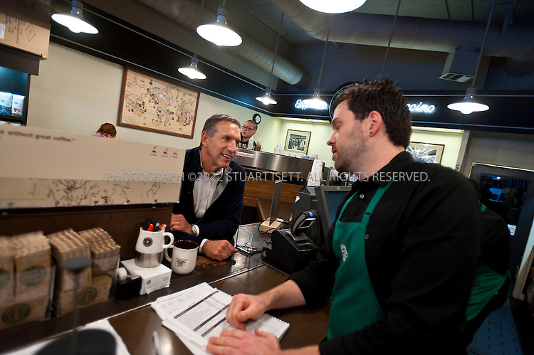 2/16/2011--Seattle, WA, USA...Howard Schultz has a key that opens the Starbucks at Pike Place Market (1912 Pike Place), in Seattle, WASH., and he often comes in the early mornings and lets himself into the store. Starbucks opened its first store in 1971 in the Market in downtown Seattle. Because the Market is a historic district with design guidelines, the store retains its original look. Here Schultz is talking with stire manager Chad Moore (39)...©2011 Stuart Isett. All rights reserved.