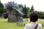"""July 18, 2014, Tokyo, Japan - A woman takes pictures of the 6.6 meter model of the new Godzilla at Tokyo Midtown on July 18, 2014, Tokyo. The statue is a 1/7 scale reproduction of the 180 meters tall Hollywood film version of """"GODZILLA"""".  Godzilla and its footprints will be displayed from July 18 to August 31 during which time it will perform a special show using mist, light and sound effects every 30 minutes between 19:00 to 21:00. (Photo by Rodrigo Reyes Marin/AFLO)"""