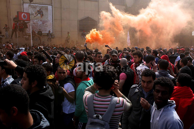 "Egyptian soccer fans of Al-Ahly club celebrate in front of their club premises in Cairo, Egypt, Saturday, March 9, 2013. An Egyptian court confirmed death sentences against 21 people for their role in a deadly 2012 soccer riot that killed more than 70 people in the city of Port Said. Banner at background showing some pictures of the victims with Arabic that reads, ""we will never forget you"". Photo by Tareq Gabas"