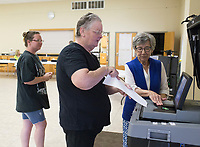NWA Democrat-Gazette/CHARLIE KAIJO Brenda Taylor (right) helps Charlotte Atkins of Garfield (center) enter her ballot during an election, Friday, July 5, 2019 at the NEBCO Community Building in Garfield. <br /> <br /> The Northeast Benton County Fire Department is holding a special election to increase fire dues.