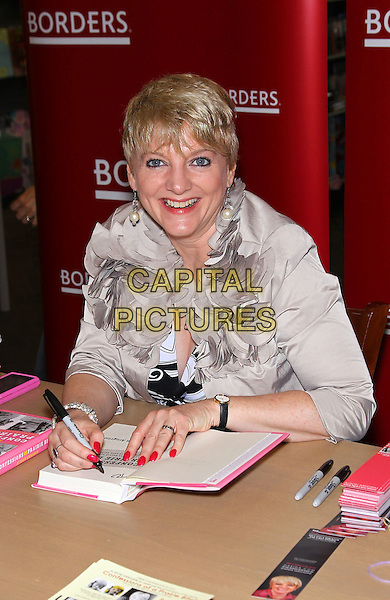 "ALISON ARNGRIM.signs copies of her book ""Confessions of a Prairie Bitch""  at Borders Book Store at Town Center,  Las Vegas, Nevada, USA, 7th August 2010..half length sitting signing smiling dress black and white print silver jacket bolero ruffles .CAP/ADM/MJT.© MJT/AdMedia/Capital Pictures."
