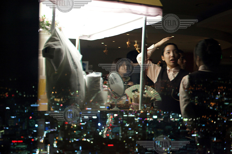 A reflection in a window of the N Seoul Tower, overlooking the city at night.