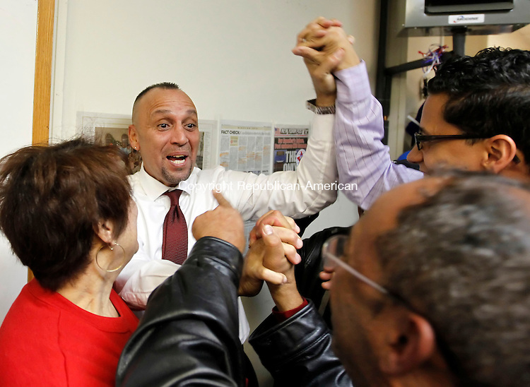 """Waterbury, CT-06 November 2012-110612CM13-  Victor Cuevas, center, Democratic candidate for the 75th District  celebrates with BJ Rodriguez, Team Leader for the 75th District Democratic Town Committee, right, and Dolly Rosario, of Waterbury, left, after at his headquarters Tuesday night in Waterbury.  Cuevas  defeated Republican John """"Jack"""" Alseph Jr.     Christopher Massa Republican-American"""