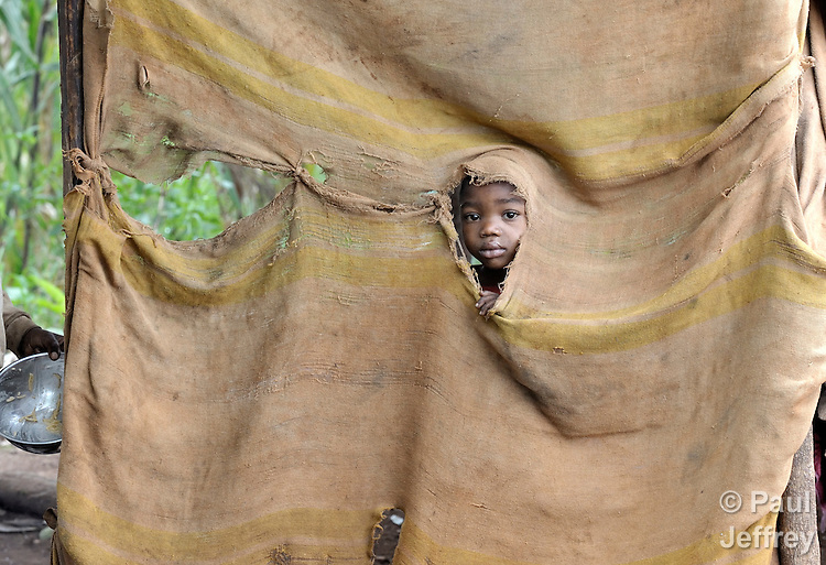 """A child peeks through the """"wall"""" of a poor house in the Haitian village of Foret des Pins."""