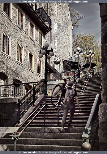 Person with a bike walking up on the stairs of historic street Rue du Petit Champlain of Old Quebec City. Le Repaire restaurant sign in the background. Quebec, Canada. Ville de Québec.