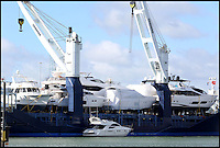 BNPS.co.uk (01202 558833)<br /> Pic: CorinMesser/BNPS<br /> <br /> ****Please use full byline****<br /> <br /> A precious cargo of luxury motorboats worth &pound;25 million are loaded onto an enormous cargo ship for a piggy-back ride to their new wealthy Mediterranean owners.<br /> <br /> Seven plush powerboats made by Sunseeker carefully craned onto a special 300ft transporter ship at the company's boatyard in Poole, Dorset.<br /> <br /> The boats are destined for a number of undisclosed millionaire's resorts around the Mediterranean.<br /> <br /> Included in the shipment were two Sunseeker 28 Metre Yachts each worth &pound;6 million plus one Predator 115 which sells for &pound;11 million.<br /> <br /> It comes weeks after the firm unveiled the biggest boat ever built in the UK - a whopping 155ft superyacht made for Formula One mogul Eddie Jordan for an estimated &pound;32 million.