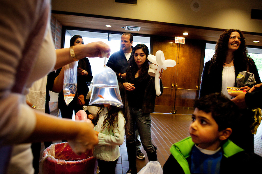 Los Angeles, California, March 20, 2011 - Bags of goldfish are handed to children during a Purim carnival at Stephen S. Wise Temple. The goldfish are used in the Persian New Year celebration, Nowruz. The Stephen S. Wise Temple is a reform synagogue with a strong Persian congregation. ..Purim is a Jewish holiday that commemorates the deliverance of the Jewish people living in the Persian Empire from genocide at the hands of the political advisor, Haman, to the Persian King Ahasuerus, as documented in the Talmud's Book of Esther. It is celebrated by the reading of the Scroll of Esther or the Megillah, sending food gifts to friends, giving charity to the poor and celebrating with a festive meal. During the reading of the Megillah, when Haman's name is mentioned (which happens 54 times) the congregation engages in loud roars and the use of rattles in an effort to blot out his name. Today children and some adults dress in costume and masquerade to celebrate Purim. The custom is believed to have originated during the 15th century by Italian Jews influenced by the Roman carnival. One idea for the costumes is that God disguised his presence behind many of the natural events that happened during Purim. ..Nowruz, the Persian New Year, marks the first day of spring and the beginning of the Persian calendar. It is marked by Haft Sin, or the seven S's, which include sabzeh (wheat, barley or lentil sprouts growing in a dish - symbolizing rebirth); samanu (a sweet pudding made from wheat germ -symbolizing affluence); senjed (the dried fruit of the oleaster tree - symbolizing love); s?r (garlic - symbolizing medicine); s?b (apples - symbolizing beauty and health); somaq (sumac berries - symbolizing the sunrise); serkeh (vinegar - symbolizing age and patience). Each of these items are laid on a table in the home. Other items include decorated eggs, symbolizing fertility, a mirror symbolizing cleanliness and honesty and a bowl with goldfish, symbolizing life within life. .
