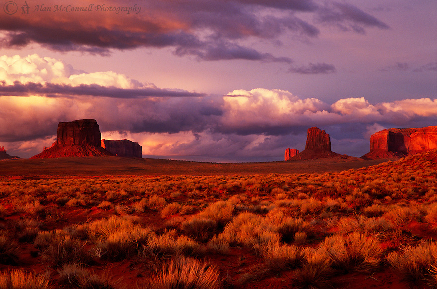 """""""Monument Valley Sunset""""<br /> Navajo National Monument, Arizona<br /> 2007<br /> <br /> Most people are aware of the fact that the best time to photograph landscapes are early in the morning or late in the evening.  The trick is to be at the exact spot, at the right time, with the perfect environmental conditions.  So, here I am, along with traveling companions Terry Lacy and Don Nelson, racing up Highway 163 trying to find a place to set up before the sun gets too low.  The low sunrays created the warm rich colors for the rock, grasses, and the stormy sky.  One minute later, it was all gone."""