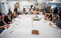 Professor Felisa Guillen's Spanish class work with professor Jocelyn Pedersen and professional bookbinder Stephanie Gibbs on their Spanish comps, printing and assembling a book with 24 essays and 6 illustrations regarding Miguel de Cervantes in celebration of his work. The Spanish comps were bound into a book that looks like the original 1605 edition of Don Quixote. April 22, 2016 in Weingart Hall.<br /> (Photo by Marc Campos, Occidental College Photographer)