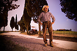 A farmer in front of the fields in Tuscany Italy with cyprus trees