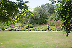 People enjoying summer flower borders in the botanical gardens at Bath, north east Somerset, England