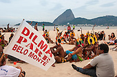 "Indigenous people and others are beginning to assemble the human banner on Flamengo beach with the Sugarloaf in the background to protest about the construction of hydroelectric dams on Brazil's rivers. One participant carries a flag, ""Dilma Pare Belo Monte"" - ""Dilma [Brazil's president] Stop Belo Monte"". The People's Summit at the United Nations Conference on Sustainable Development (Rio+20), Rio de Janeiro, Brazil, 19th June 2012. Photo © Sue Cunningham."