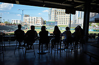 A group of fans watch the Southern Collegiate Baseball League game between the Concord Athletics and the Piedmont Pride from the concourse area at Truist Field on July 3, 2020 in Charlotte, NC. Truist Field is allowing restaurant reservations  with no more than 25 people to a space to encourage proper social distancing. The seating bowl is closed to fans at this time. (Brian Westerholt/Four Seam Images)