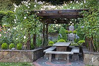 Outdoor dining nook with table and benches under arbor pergola in California backyard garden; Scales home