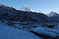 The rising sun lights the peak of Pumo Ri as the village of Lobuche is dusted with a light snow  in the Himalayan Mountains of Nepal.