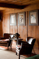 A pair of leather armchairs is placed against a wood-panelled wall displaying three vintage skiing photographs