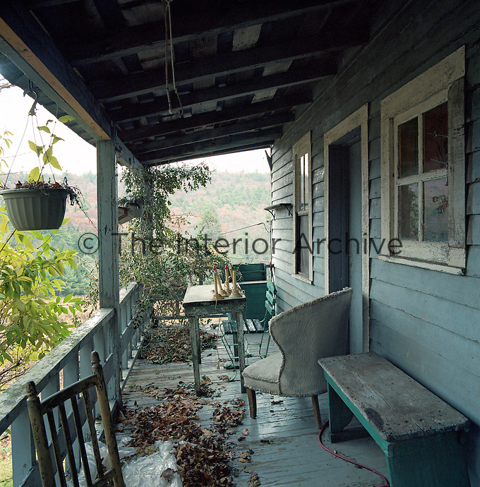 The dilapidated veranda is strewn with leaves and a collection of wooden furniture