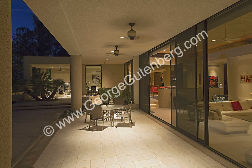 Covered patio is shown at modern home at night