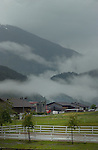 Mist and low cloud between mountains and evergreen forest, overlooking farm buildings on a dismal day. Imst district,Tyrol/Tirol. Austria.