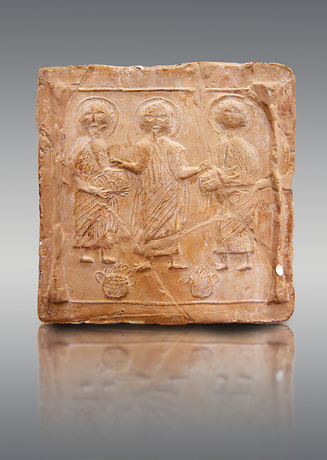 6th-7th Century Eastern Roman Byzantine  Christian Terracotta tiles depicting Christ changing Water into wine - Produced in Byzacena -  present day Tunisia. <br /> <br /> These early Christian terracotta tiles were mass produced thanks to moulds. Their quadrangular, square or rectangular shape as well as the standardised sizes in use in the different regions were determined by their architectonic function and were designed to facilitate their assembly according to various combinations to decorate large flat surfaces of walls or ceilings. <br /> <br /> Byzacena stood out for its use of biblical and hagiographic themes and a richer variety of animals, birds and roses. Some deer and lions were obviously inspired from Zeugitana prototypes attesting to the pre-existence of this province's production with respect to that of Byzacena. The rules governing this art are similar to those that applied to late Roman and Christian art with, in the case of Byzacena, an obvious popular connotation. Its distinguishing features are flatness, a predilection for symmetrical compositions, frontal and lateral representations, the absence of tridimensional atti-tudes and the naivety of some details (large eyes, pointed chins). Mass production enabled this type of decoration to be widely used at little cost and it played a role as ideograms and for teaching catechism through pictures. Painting, now often faded, enhanced motifs in relief or enriched them with additional details to break their repetitive monotony.<br /> <br /> The Bardo National Museum Tunis, Tunisia.   Against a grey background.