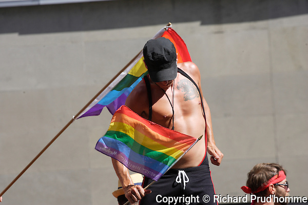 Man holding the Rainbow flag on a float at the Pride Parade in Montreal