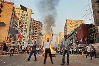 Bangladesh's opposition activists shout slogans after they burn a street vendor's cart as they clash with police during their protest in Dhaka, Bangladesh.