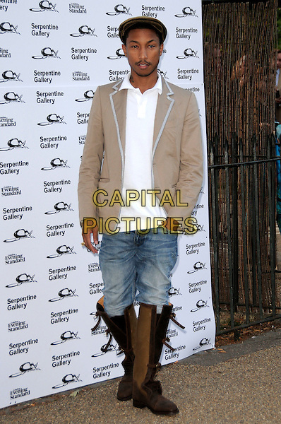 PHARRELL WILLIAMS.The Summer Party at The Serpentine Gallery, London, England. .July 9th, 2009 .full length brown boots jeans denim tucked in beige jacket hand in pocket flat cap hat.CAP/CAS.©Bob Cass/Capital Pictures.
