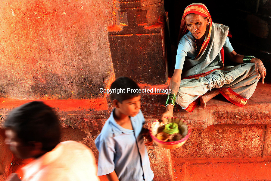 An older Devadasi woman begs at the entrance of the Yellamma Temple in Saundatti, India during the Yellamma Jatre (fesitval) . Most Devadasis over the age of 44 either beg or act as a jogati, spreading the word of Yellamma and sometimes acting as a medium through whom Yellamma speaks.  Older Devadasis are often involved in recruiting young girls to be dedicated as new Devadasis, thus perpetuating the system.