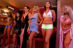 """Sex workers line up for a customer in the parlor of the Moonlite Bunny Ranch brothel in Mound House, NV on Friday, July 28, 2006...The Moonlite Bunny Ranch brothel in Mound House, Nevada - just a few miles from the state capital in Carson City - first opened in 1955. The Ranch is a legal, licensed brothel owned by Dennis Hof. It's featured in the HBO series """"Cathouse."""""""