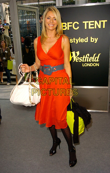 TESS DALY.The Gharani Strok Show, London Fashion Week Spring/Summer 2007, BFC Tent, Natural History Museum..September 18th, 2006.Ref: CAN.full length red orange dress grey gray belt white bag purse goody bag.www.capitalpictures.com.sales@capitalpictures.com.©Can Nguyen/Capital Pictures