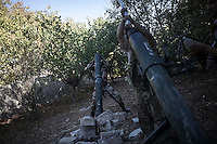 In this Monday, Oct. 07, 2013 photo, opposition fighters reload pieces of heavy artillery during an attack over Wadi Al-Deef military post at the frontline in Maraat Anouman in the Idlib province countryside of Syria. (AP/Photo)