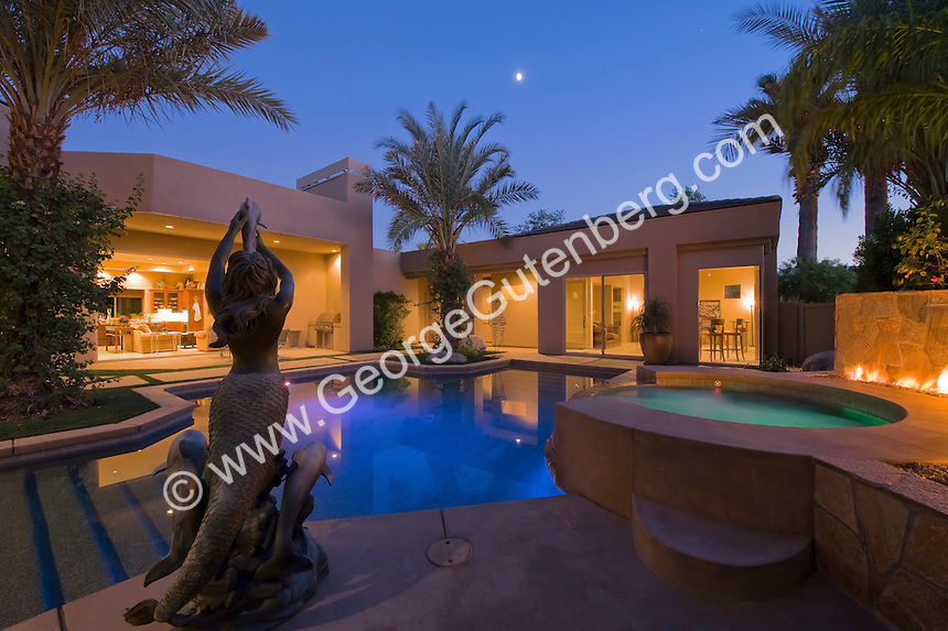 Night time view of pool are in courtyard with a fire feature and moon rising