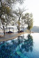 Covered daybeds beside the swimming pool at the Singita Pamushana Lodge, Malilongwe Trust, Zimbabwe