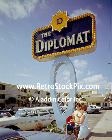 Diplomat Hotel, Myrtle Beach, SC. Two ladies mailing a letter by the large Diplomat neon sign.